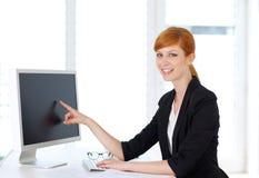 Geschäftsfrau, die Inhalt auf Computer zeigt Stockfotografie