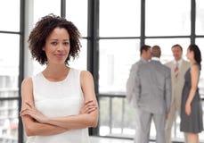 Geschäftsfrau, die innen vom Geschäftsteam lächelt stockfotos