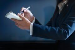 Geschäftsfrau, die Kenntnisse im Papier auf dunkelblauem Hintergrund nimmt lizenzfreie stockbilder