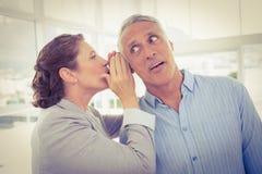 Geschäftsfrau, die Klatsch zu ihrem Kollegen flüstert stockfoto