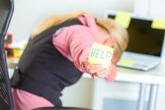 Geschäftsfrau, die klebrige Anmerkung mit Hilfenwort zeigt lizenzfreie stockfotografie