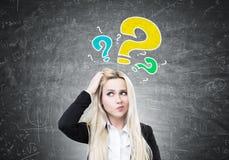 Geschäftsfrau, die Kopf, Fragen verkratzt Lizenzfreies Stockfoto