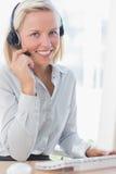Geschäftsfrau, die Kopfhörer verwendet und an der Kamera lächelt Stockfotografie