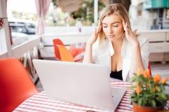 Geschäftsfrau, die Kopfschmerzen beim Arbeiten unter Verwendung der Laptop-Computers hat Stockfotografie