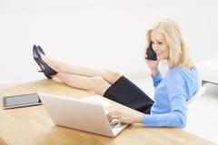 Geschäftsfrau, die an Laptop im Büro arbeitet Stockfotos