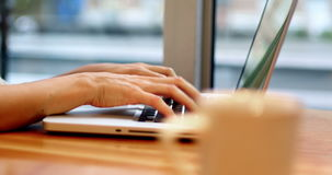 Geschäftsfrau, die Laptop mit Kaffeetasse auf Tabelle verwendet stock video footage