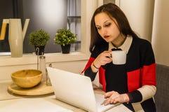 Geschäftsfrau, die an Laptop und trinkendem heißem Kaffee arbeitet Lizenzfreies Stockfoto