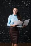 Geschäftsfrau, die Laptop, Vorderansicht steht und hält Dachbodenbacksteinmauer am Hintergrund Konzept der Arbeit Stockfotografie