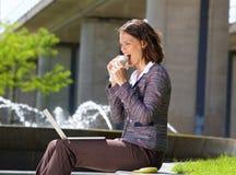 Geschäftsfrau, die Lebensmittel während der Mittagspause isst Lizenzfreies Stockfoto
