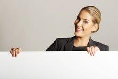 Geschäftsfrau, die leere Anschlagtafel anhält Stockfoto