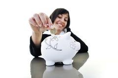 Geschäftsfrau, die Münzengeld in piggy Querneigung einsetzt Lizenzfreie Stockbilder