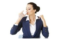 Geschäftsfrau, die Mineralwasser trinkt Stockbild