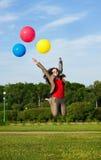 Geschäftsfrau, die mit Ballonen springt Lizenzfreies Stockbild