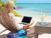 Geschäftsfrau, die mit Computer auf dem Strand arbeitet