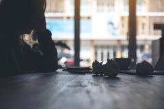 Geschäftsfrau, die mit dem Gefühl frustriert und mit geschraubt herauf Papiere und Laptop auf Tabelle im Büro betont arbeitet lizenzfreie stockfotos