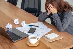 Geschäftsfrau, die mit dem Gefühl frustriert und mit geschraubt herauf Papiere und Laptop auf Tabelle im Büro betont arbeitet stockfoto