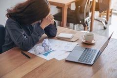 Geschäftsfrau, die mit dem Gefühl frustriert und mit geschraubt herauf Papiere und Laptop auf Tabelle im Büro betont arbeitet stockfotografie