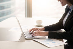 Geschäftsfrau, die mit Diagrammen im Büro unter Verwendung des Laptops, clos arbeitet Lizenzfreie Stockfotos
