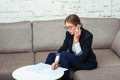 Geschäftsfrau, die mit Dokumenten auf Sofa arbeitet lizenzfreie stockbilder