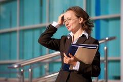 Geschäftsfrau, die mit Dokumenten und Laptop sitzt Stockbild