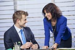 Geschäftsfrau, die mit einem Mann im Büro flirtet Stockbilder