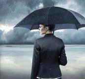 Geschäftsfrau, die mit einem Regenschirm steht Stockfoto