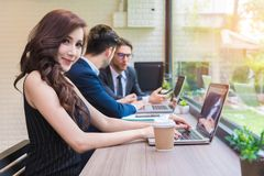 Geschäftsfrau, die mit Geschäftsteam durch Laptop-Computer arbeitet Seien Sie stockfoto