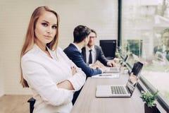 Geschäftsfrau, die mit Geschäftsteam durch Laptop-Computer arbeitet Seien Sie Stockbilder
