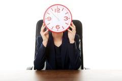 Geschäftsfrau, die mit großer Uhr im Büro sitzt Stockbild
