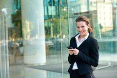 Geschäftsfrau, die mit Handy außerhalb des Bürogebäudes lächelt Lizenzfreie Stockfotos