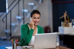 Geschäftsfrau, die mit ihrem Handy lächelt und nennt stockbild