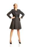 Geschäftsfrau, die mit ihren Händen auf Hüften steht stockbild