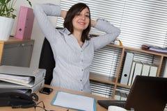 Geschäftsfrau, die mit ihren Händen hinter ihrem Kopf sich entspannt Lizenzfreie Stockfotos