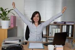 Geschäftsfrau, die mit ihren Händen oben sich entspannt Lizenzfreie Stockfotos