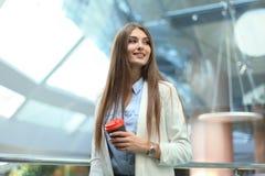 Geschäftsfrau, die mit Kaffee in der Papierschale im Büro steht lizenzfreie stockfotos