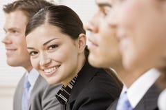 Geschäftsfrau, die mit Kollegen aufwirft Stockbilder