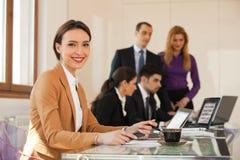 Geschäftsfrau, die mit Kollegen im Hintergrund lächelt stockbild