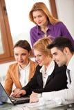 Geschäftsfrau, die mit Kollegen im Hintergrund lächelt stockbilder