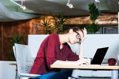 Geschäftsfrau, die mit Laptop arbeitet und Kopfschmerzen im Büro hat Stockfotos
