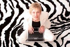 Geschäftsfrau, die mit Laptop sitzt Stockbild
