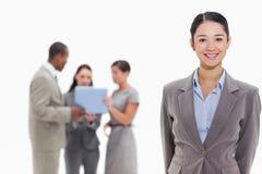 Geschäftsfrau, die mit Mitarbeitern im Hintergrund lächelt Stockbild