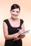 Geschäftsfrau, die mit Notizblock lächelt Lizenzfreie Stockfotografie