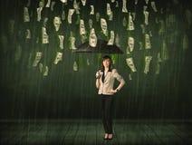 Geschäftsfrau, die mit Regenschirm im Dollarschein-Regenkonzept steht Stockfotografie