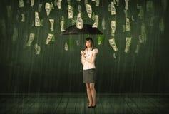 Geschäftsfrau, die mit Regenschirm im Dollarschein-Regenkonzept steht Stockfoto