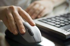 Geschäftsfrau, die mit schwarzer Computermaus arbeitet. Lizenzfreies Stockfoto