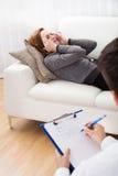 Geschäftsfrau, die mit seinem Psychiater erklärt etwas spricht Lizenzfreie Stockfotos