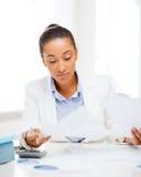 Geschäftsfrau, die mit Taschenrechner im Büro arbeitet Stockfoto