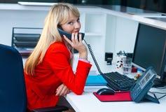 Geschäftsfrau, die mit Telefon im Büro spricht Lizenzfreies Stockbild
