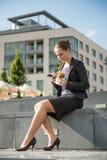 Geschäftsfrau, die mit Telefon isst und arbeitet Lizenzfreie Stockfotos