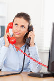 Geschäftsfrau, die mit zwei Telefonen telefoniert Stockfotografie